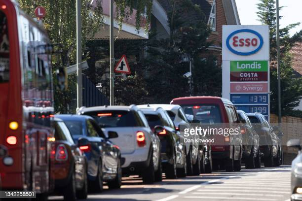 Queue forms for an Esso petrol station on September 24, 2021 in London, United Kingdom. BP and Esso have announced that its ability to transport fuel...
