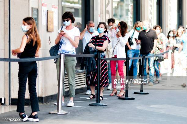 queue in front of a shop, during pandemic covid19 in europe. people must wear a surgical mask. - waiting in line stock pictures, royalty-free photos & images