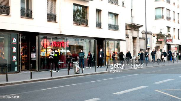 queue in front of a supermarket during pandemic 2020 in europe. - confined space stock pictures, royalty-free photos & images