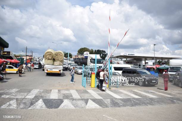 Queue of cars are seen at the Maseru Bridge border post between Lesotho and South Africa on March 24 as residents and retailers of Lesotho head to...