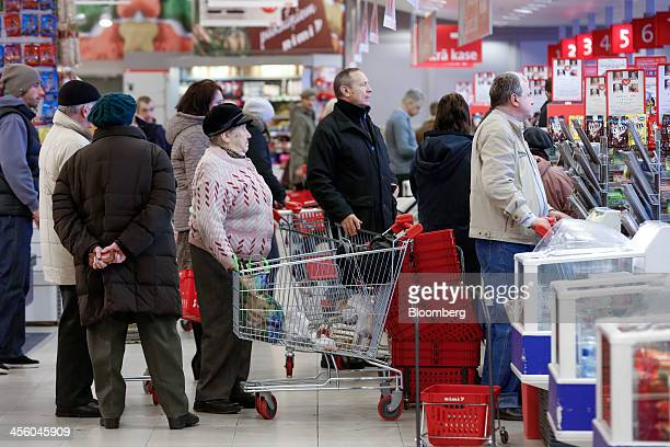 A queue of customers wait for service at the checkout desk inside a Rimi Baltic supermarket in Riga Latvia on Monday Dec 9 2013 The country of 2...