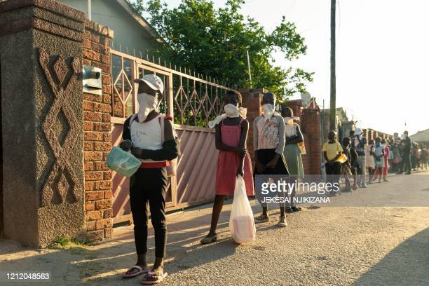 A queue of needy individuals with plates in hand forms outside Samantha Murozoki's home in Chitungwizaon May 5 where she feeds the underprivileged a...
