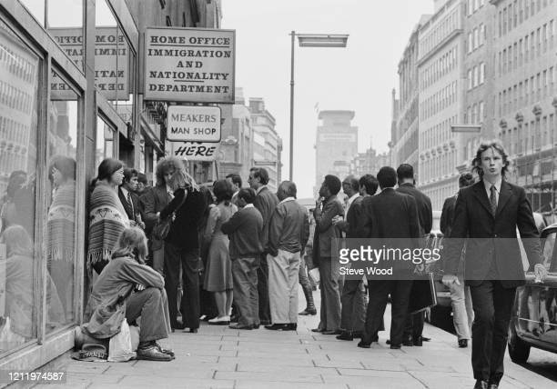 Queue of people form at the entrance to the offices of the Home Office Immigration and Nationality Department on High Holborn in London, England, 4th...