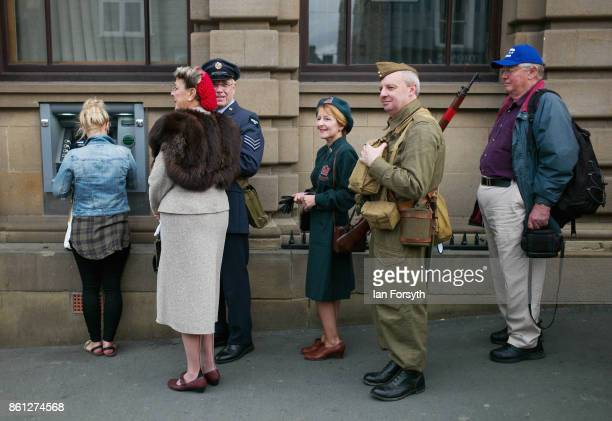 A queue of people some in period clothing wait at a cash machine during the North Yorkshire Moors Railway 1940's Wartime Weekend event on October 14...