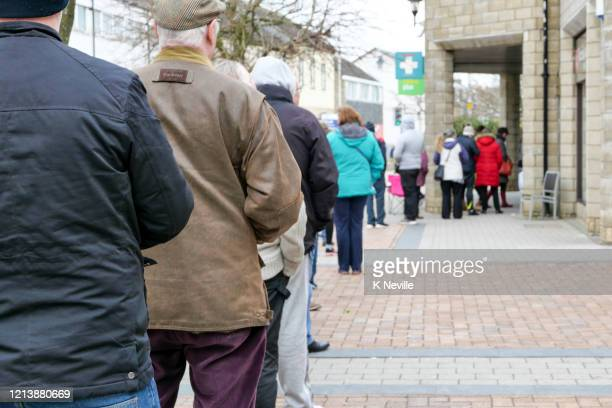 queue of people trying to get their prescriptions, as people panic over coronavirus - waiting in line stock pictures, royalty-free photos & images