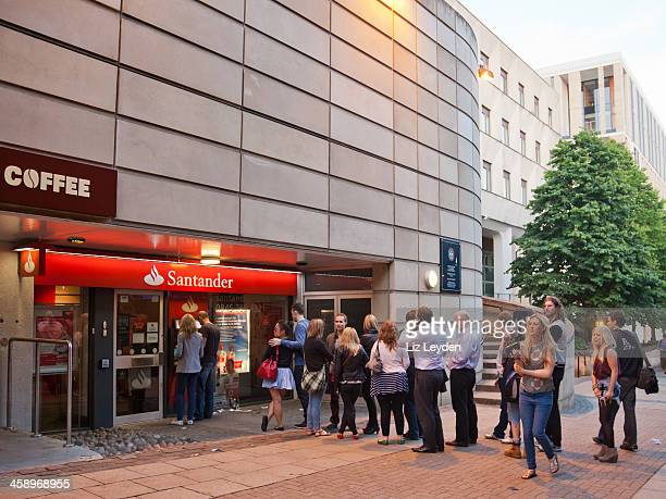 Queue of people waiting at a Santander ATM; central Edinburgh