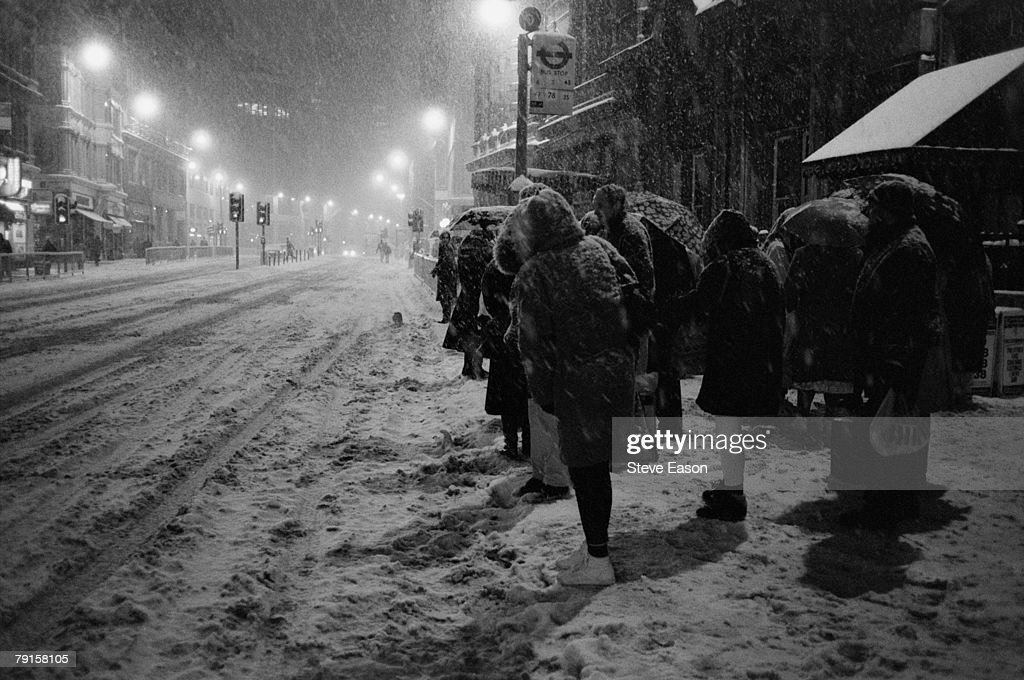 a queue of people waiting for a bus in heavy snow london january