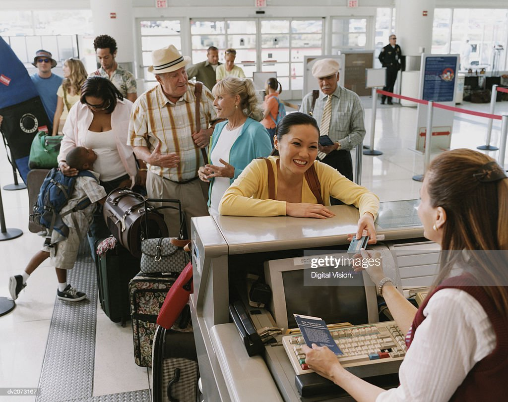 Queue of Tourists at an Airport Check-In Desk : Stock Photo