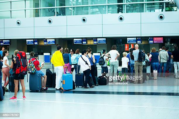 Queue of travelling people at check-in into holidays