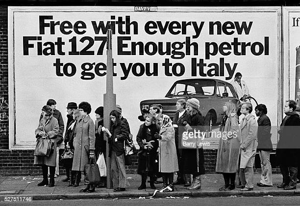 Queue waiting for bus in North Kensington in front of Fiat advertising poster The Fiat 127 was one of the first of the modern superminis and won...