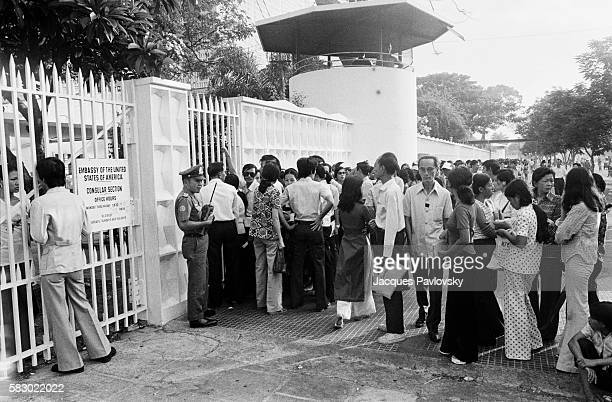 Queues form outside the American Embassy in the hope of securing visas available to wives Vietnamese mothers married to Americans and staff working...