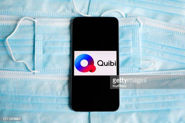 Quibi logo is displayed on a mobile phone screen photographed on surgical masks background for illustration photo during the spread of coronavirus...