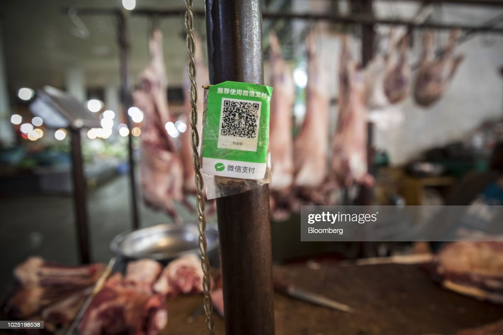 A quick respond (QR) code for Tencent Holdings Ltd.'s WeChat Pay service is displayed at a mutton stall in a market in Golmud, Qinghai province, China, on Sunday, July 22, 2018. Amid rising fears about a trade war, China's policy makers have unveiled measures to boost infrastructure construction and credit to smaller firms, as well as tax cuts. Photographer: Qilai Shen/Bloomberg via Getty Images