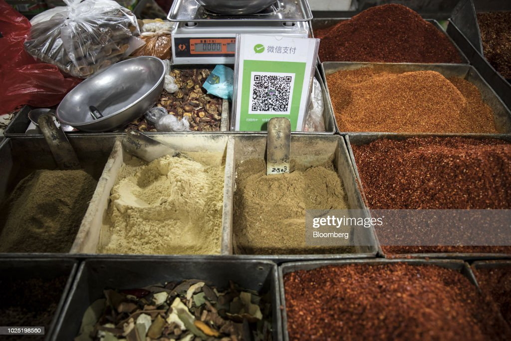 A quick respond (QR) code for Tencent Holdings Ltd.'s WeChat Pay service stands among tubs of spices for sale at a market stall in Golmud, Qinghai province, China, on Sunday, July 22, 2018. Amid rising fears about a trade war, China's policy makers have unveiled measures to boost infrastructure construction and credit to smaller firms, as well as tax cuts. Photographer: Qilai Shen/Bloomberg via Getty Images