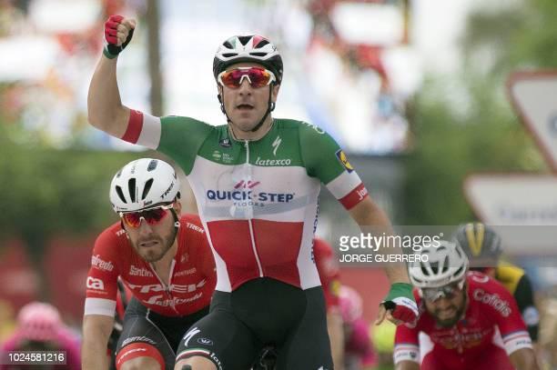 Quick - Step Floors' Italian cyclist Elia Viviani celebrates crossing the finish line followed by Trek - Segafredo's Italian cyclist Giacomo Nizzolo...
