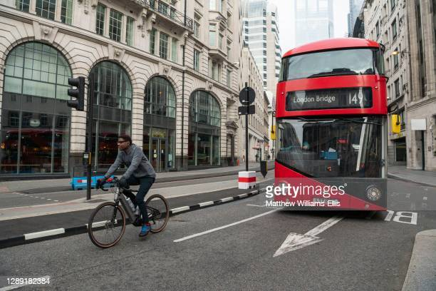 Quiet roads and streets in the City in central London with just a red London Bus for public transport, and a cyclist on a bicycle taken during...