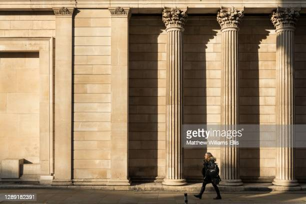 Quiet streets of London in England during Coronavirus Covid-19 lockdown at Bank of England in The City, at rush hour and one person walking alone,...