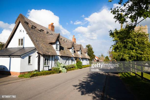 Quiet Suffolk quaint traditional village street Church and houses in spring sun with clouds