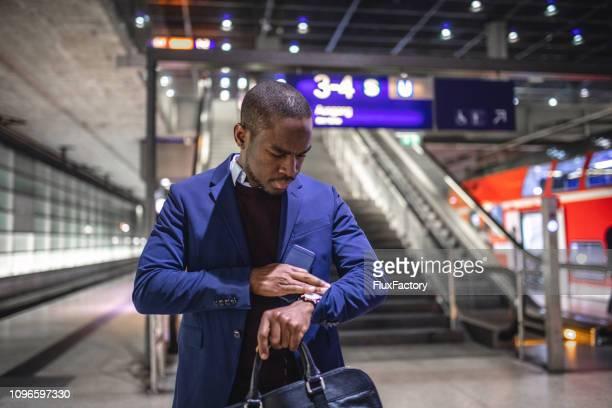 rustig succesvol zakenman, de tijd op zijn horloge tijdens het wachten voor zijn trein controleren - polshorloge stockfoto's en -beelden