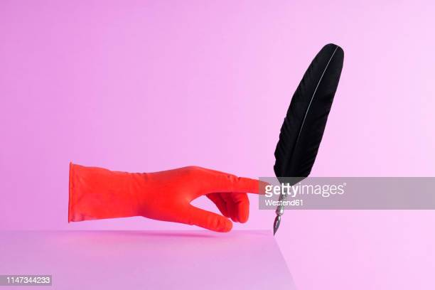 quill pen pushed over the edge over pink background - purple glove stock pictures, royalty-free photos & images