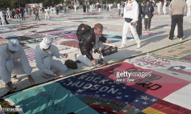 Quilt monitors along with a photographer adjust a panel in the NAMES Project AIDS Memorial Quilt as it is displayed on the National Mall Washington...