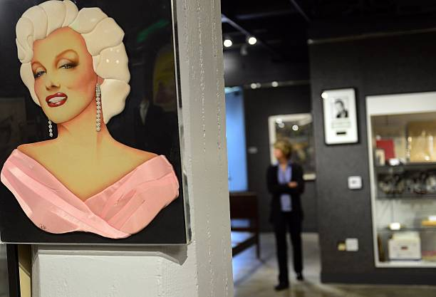 A quilted portrait image of Marilyn Monroe with airbrushed facial features part of a group of Marilyn Monroe memorabilia estimated between $300 and...