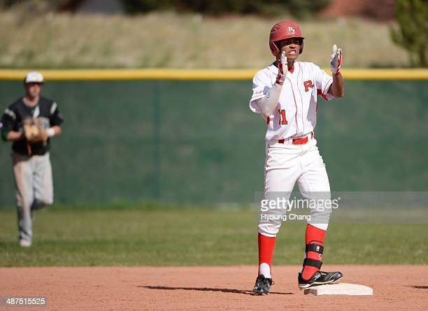 Quin Cotton of Regis Jesuit High School celebrate his double from Nick Leonard of Mountain Vista High School in the 1st inning of the game at Regis...