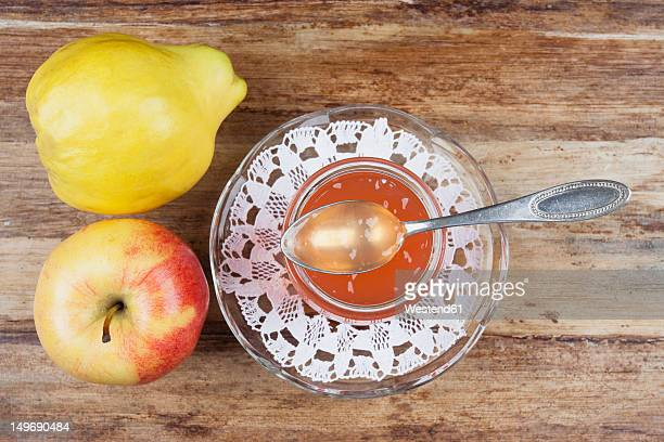 Quince and apple jam in jar with fruit on table