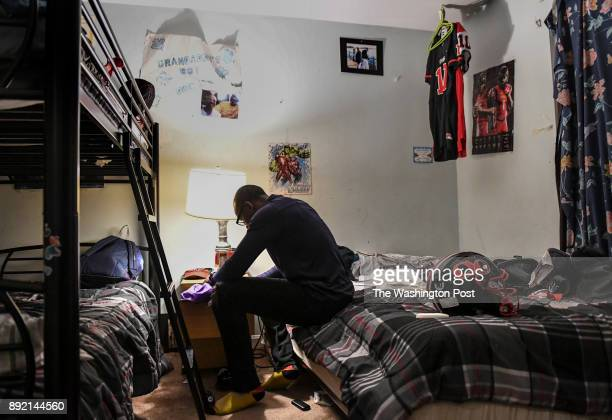 GAITHERSBURG MD NOVEMBER Quince Orchard senior quarterback Doc Bonner searches a nightstand for his socks as he gets his uniform ready the night...
