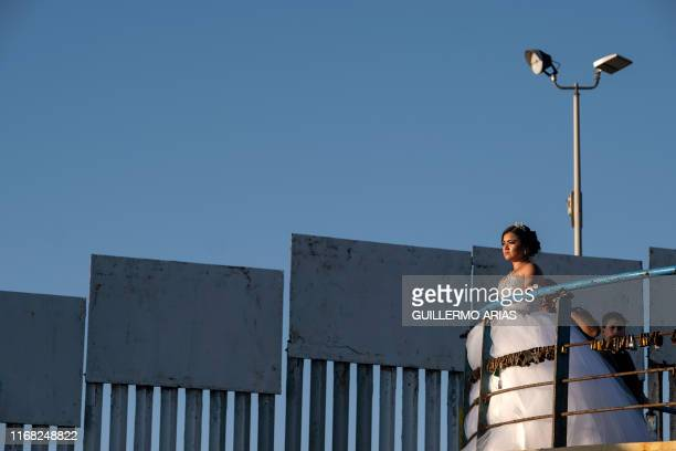 TOPSHOT A quinceanera stands for her portrait to be taken near the USMexico border fence in Playas de Tijuana on September 14 Baja California state...