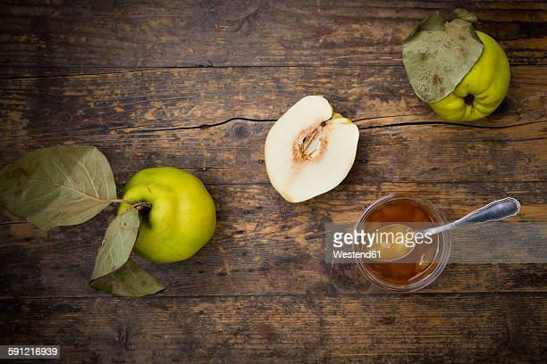 Quinces and a glass of quince jam on wood