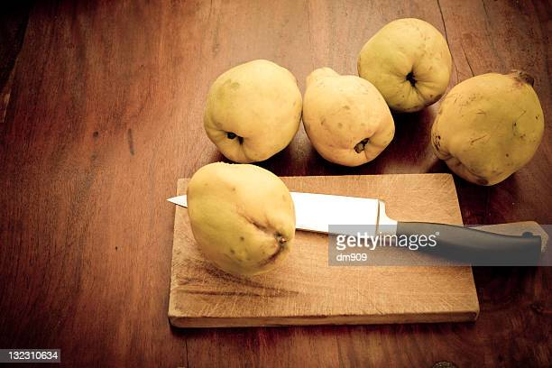 Quinces on wooden table with knife