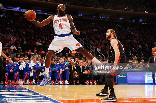 Quincy Acy of the New York Knicks in action against Josh McRoberts of the Miami Heat at Madison Square Garden on November 30 2014 in New York City...