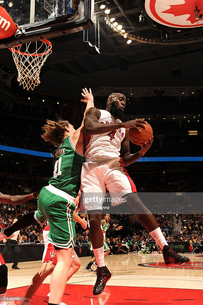 Quincy Acy #4 of the Toronto Raptors grabs a rebound against Kelly Olynyk #41 of the Boston Celtics during the game on October 16, 2013 at the Air Canada Centre in Toronto, Ontario, Canada.