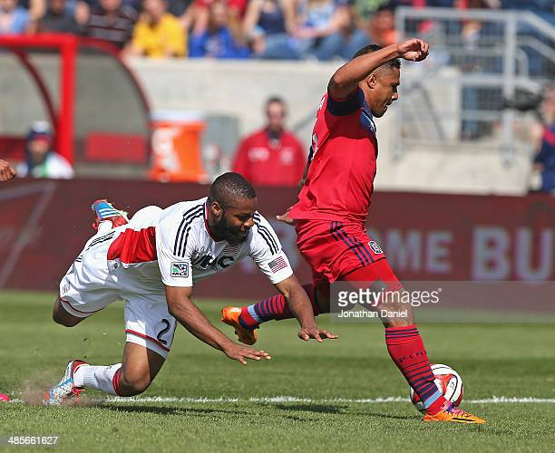 Quincy Amarikaw of the Chicago Fire shoots and scores a goal as Andrew Farrell 2 of the New England Revolution hits the ground during an MLS match at...