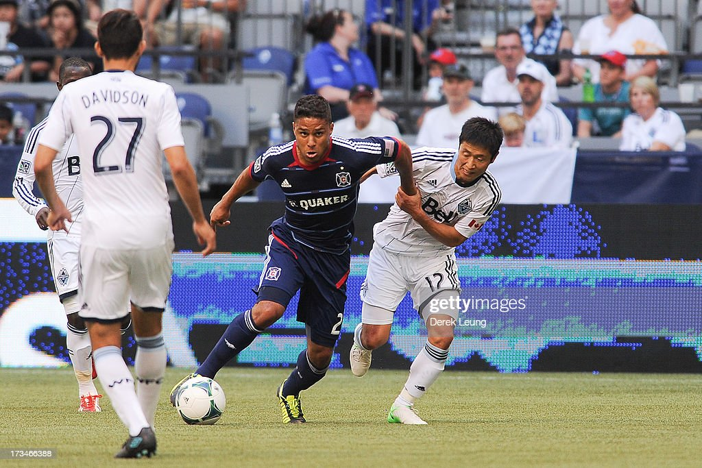 Quincy Amarikwa #24 of Chicago Fire dribbles the ball past Young-Pyo Lee #12 of the Vancouver Whitecaps during an MLS Match at B.C. Place on July 14, 2013 in Vancouver, British Columbia, Canada. The Vancouver Whitecaps won 3-1.