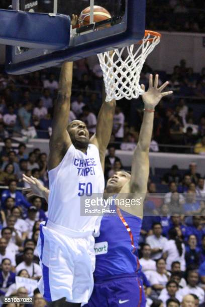 Quincy Davis III of Chinese Taipei tries to dunk the ball over Junemar Fajardo of the Philippines Gilas Pilipinas defeated the visiting Chinese...