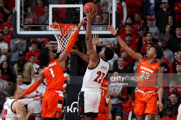 Quincy Guerrier and Elijah Hughes of the Syracuse Orange defend against Steven Enoch of the Louisville Cardinals in the first half of a game at KFC...