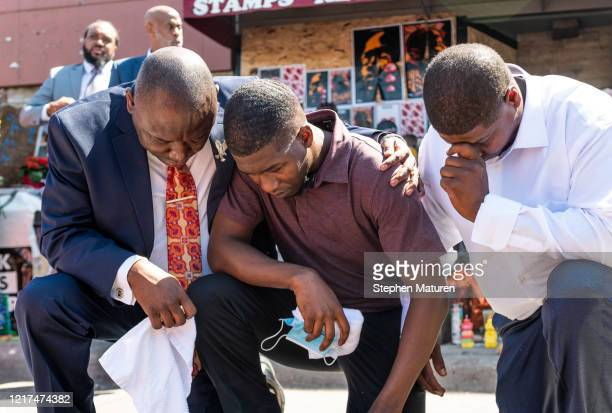 Quincy Mason Floyd son of George Floyd and attorney Ben Crump kneel at the site where Floyd was killed on June 3 2020 in Minneapolis Minnesota Crump...