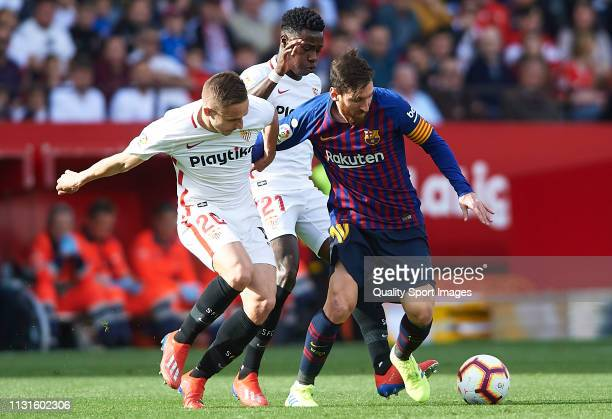 Quincy Promes of Sevilla and his teammate Marko Rog compete for the ball with Lionel Messi of Barcelona during the La Liga match between Sevilla FC...