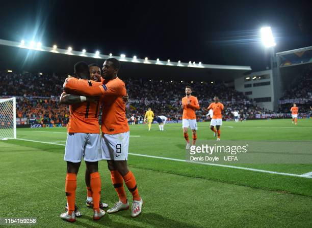 Quincy Promes of the Netherlands celebrates with Memphis Depay and Georginio Wijnaldum of the Netherlands after scoring his sides third goal during...
