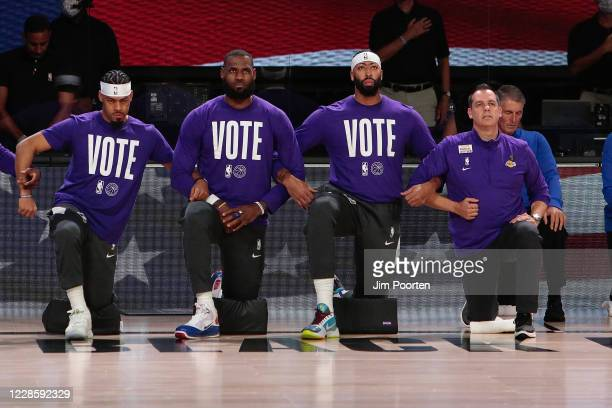 Quinn Cook LeBron James Anthony Davis and Head Coach Frank Vogel of the Los Angeles Lakers during the national anthem against the Denver Nuggets in...