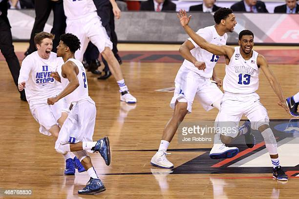Quinn Cook Matt Jones and Jahlil Okafor of the Duke Blue Devils celebrate with teammates after defeating the Wisconsin Badgers during the NCAA Men's...