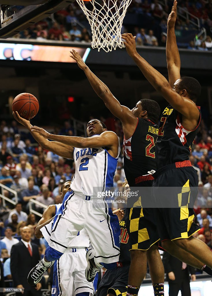 Quinn Cook #2 of the Duke Blue Devils goes up for a shot against the defense of Pe'Shon Howard #21 and Dez Wells #32 of the Maryland Terrapins in the first half of their game during the quarterfinals of the ACC Men's Basketball Tournament at Greensboro Coliseum on March 15, 2013 in Greensboro, North Carolina.