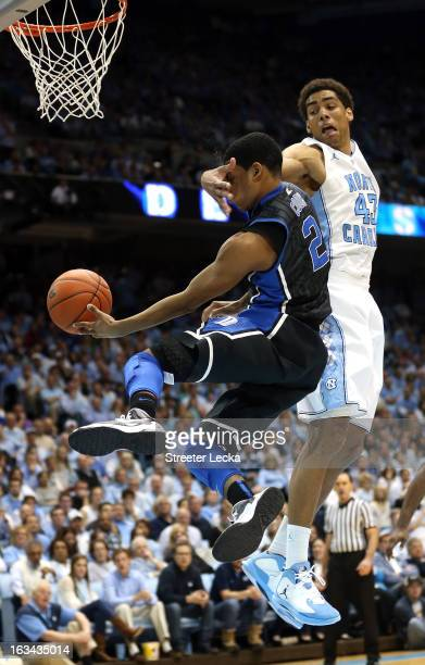 Quinn Cook of the Duke Blue Devils is hit in the face on his way to the basket by James Michael McAdoo of the North Carolina Tar Heels during their...