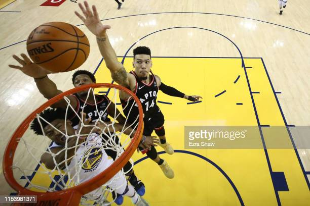 Quinn Cook of the Golden State Warriors attempts a shot past Kyle Lowry and Danny Green of the Toronto Raptors in the second half during Game Three...