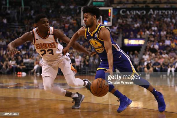 Quinn Cook of the Golden State Warriors drives the ball past Danuel House Jr #23 of the Phoenix Suns during the first half of the NBA game at Talking...