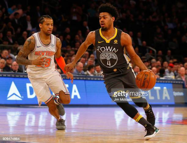 Quinn Cook of the Golden State Warriors in action against Trey Burke of the New York Knicks at Madison Square Garden on February 26 2018 in New York...