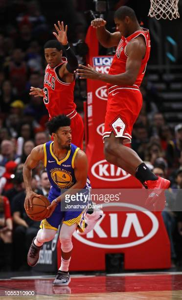 Quinn Cook of the Golden State Warriors looks to pass as Shaquille Harrison and Cristiano Felicio of the Chicago Bulls leap behind him at the United...
