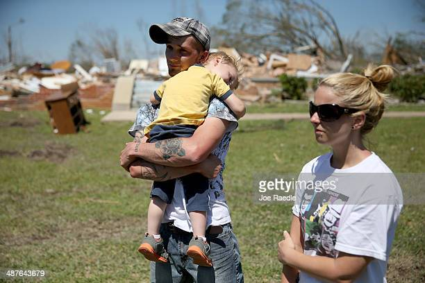 Quinn Daniel holds his son Peyton Daniel as he stands with his wife Rebekah Daniel in front of what is left of their house after it was destroyed...